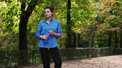 Woman standing in the park with energy drink, slow motion shot at 240fps, steady Stock Footage