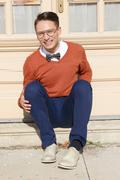man with glasses and sweater sitting on steps in front of house and posing - stock photo
