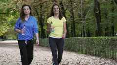 Women walking with liquids in the park, slow motion shot at 240fps, steadycam Stock Footage