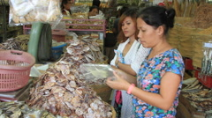 Measuring fish heads to sell at the outdoor market - stock footage
