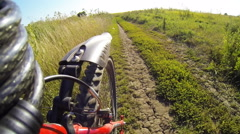 Bike rides fast on the road in the countryside. View of the rear wheel. Stock Footage