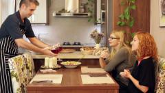 Man serving wine for women at home Stock Footage