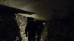 Men Walking Thru Catacomb Stone Tunnel Stock Footage