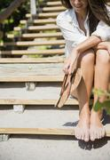 Caucasian woman with sandy feet sitting on beach staircase Stock Photos
