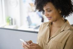 Businesswoman using cell phone in cubicle Stock Photos