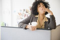 Businesswoman with cup of coffee yawning in cubicle Stock Photos