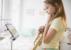 Caucasian girl practicing trumpet with digital tablet Stock Photos