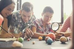 Students examining models of planets in classroom Stock Photos