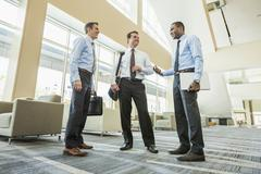 Low angle view of businessmen talking in office lobby Stock Photos