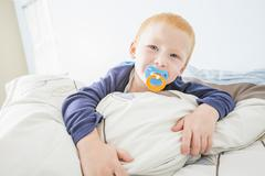 Caucasian boy sucking pacifier in bed Stock Photos