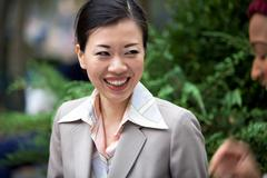 an attractive asian woman dressed in business attire laughing at the words of - stock photo