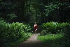Korean woman running in lush forest Stock Photos