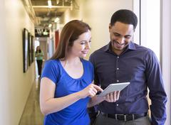 Business people using digital tablet in office hallway Stock Photos