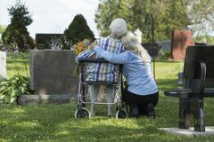Caucasian mother and daughter visiting grave in cemetery Stock Photos