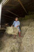 Older Caucasian woman hauling hay bales in barn Stock Photos