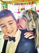 Caucasian mother kissing son in tuxedo at birthday party Stock Photos