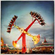 Illuminated amusement park ride under cloudy sky Kuvituskuvat