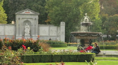 Green city park with fountain, mother with buggy, architecture Stock Footage