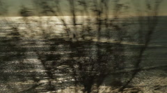 Traveling on train, looking out window viewing bushes & waves-11 Stock Footage