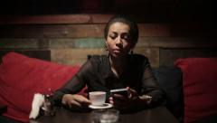 Black woman drinking hot coffee and use smartphones Stock Footage