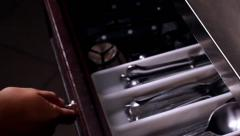 Extreme closeup of putting away silverware in a drawer - stock footage