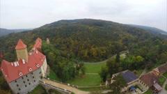 Medieval European castle red rooftops, aerial shot, brown trees Stock Footage