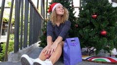 Cheerful Santa Helper Girl with Gift Bag near Christmas Tree. Stock Footage