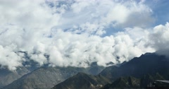 4k puffy clouds mass rolling over Tibet mountaintop & valley,roof of the World. Stock Footage