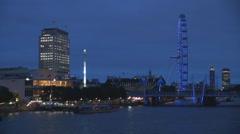 Illuminated Ferris wheel Hungerford Bridge twilight night light London Downtown  Stock Footage