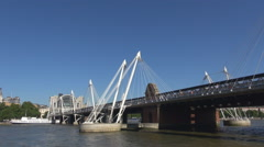 Hungerford Bridge cross Thames River Downtown London famous city landmark sunny  Stock Footage