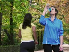 Sporty woman drinking energy drink, slow motion shot, steadycam shot Stock Footage