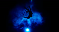Aerial acrobat woman on circus stage. Silhouette on a blue background. Stock Footage