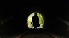 Lost woman walks towards end of dark tunnel, light ahead Stock Footage