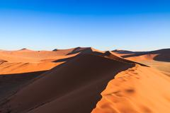 walking to top red dune of always shifting sand. sossusvlei, namibia, africa. - stock photo