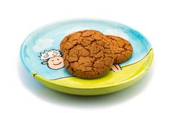 Smiling sheep underneath cookies on a colorful plate Stock Photos
