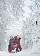 boy and girl at sledging through snowy - stock photo