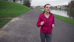 Young woman jogging on path by city river HD Stock Footage