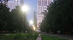 People walk along the boulevard near living complex at evening Stock Footage