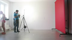 Work in the studio: photographer shooting a young guy who sings Stock Footage