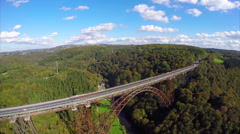 Beautiful landscape above old steel railroad train bridge aerial Stock Footage
