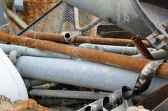 rusted iron pipes of a landfill of ferrous material - stock photo