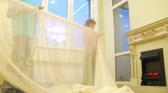 Two children put curtains on a curtain rod at a light room Stock Footage