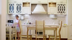 Girl sets the table in light kitchen. Time lapse. Stock Footage
