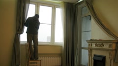 Worker measures the windows in living room and install jalousie Stock Footage