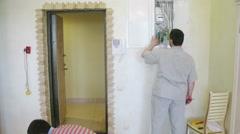 Workers mounts Intercom in light room near the doorway Stock Footage