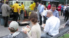 People are queuing around the street stalls The Halal Guys. Stock Footage