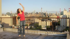 Woman dancing on roof of building, then to daughter joins. Stock Footage