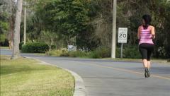 Woman running alongside road Stock Footage
