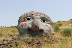 stone face sculpture on mount vesuvius in naples demolished by graffiti - stock photo