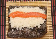 raw salmon on nori algae and rice - stock photo